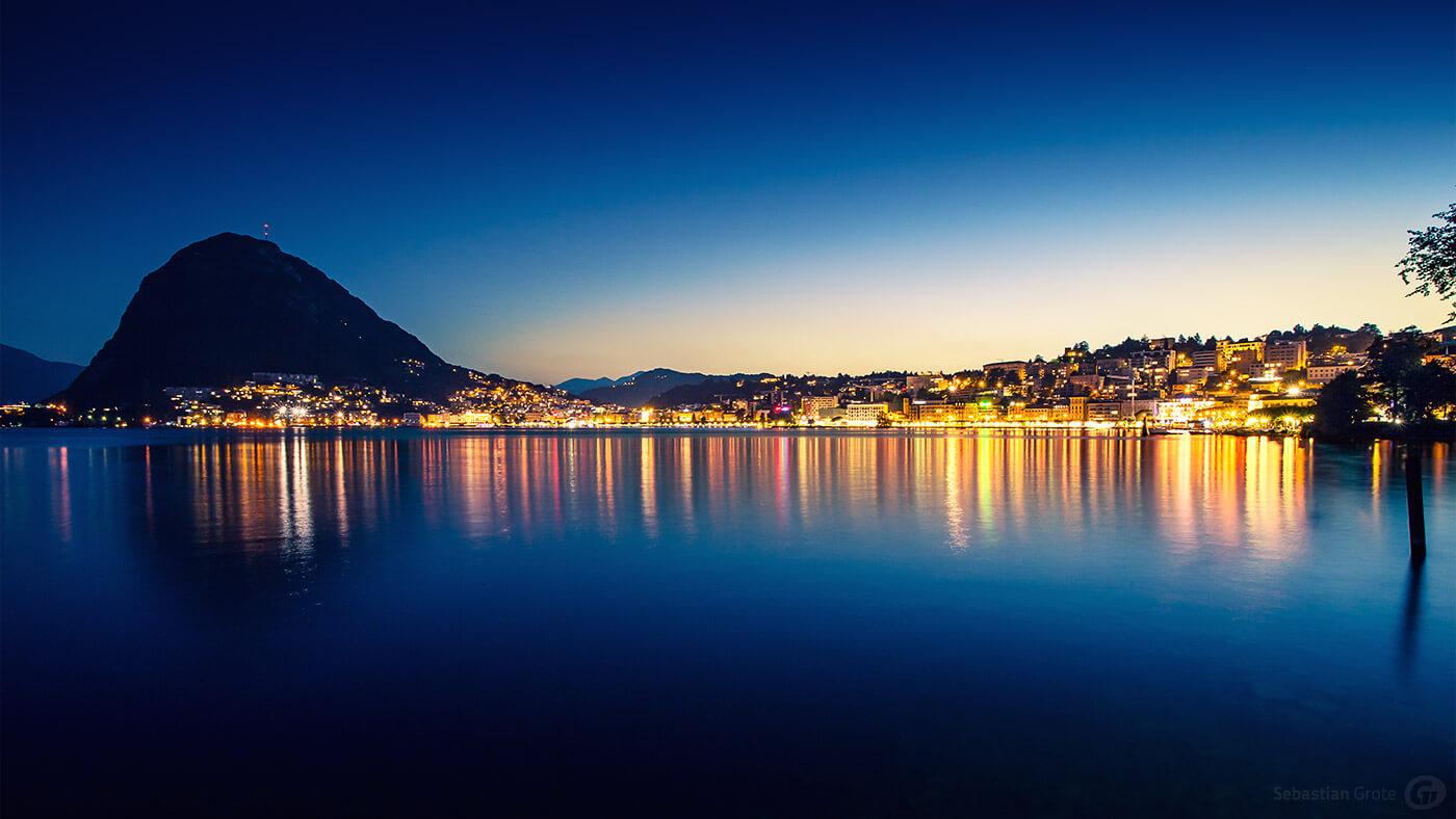 Lugano spiegelt sich im Luganer See mit Monte San Salvatore