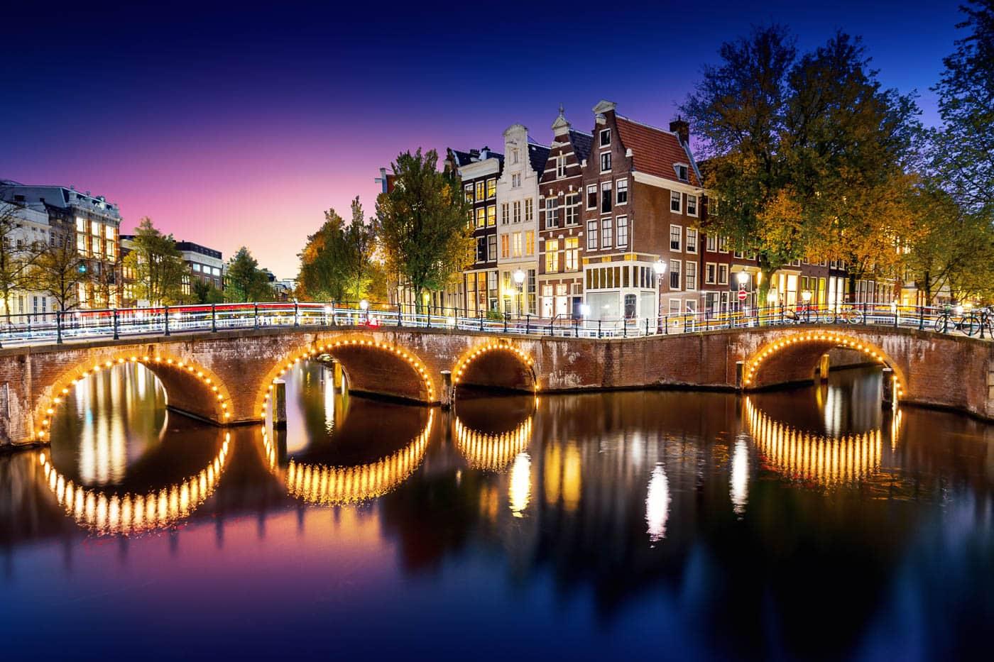 Beleuchtete Brücken an der Keizersgracht in Amsterdam, Niederlande, Nachtaufnahme